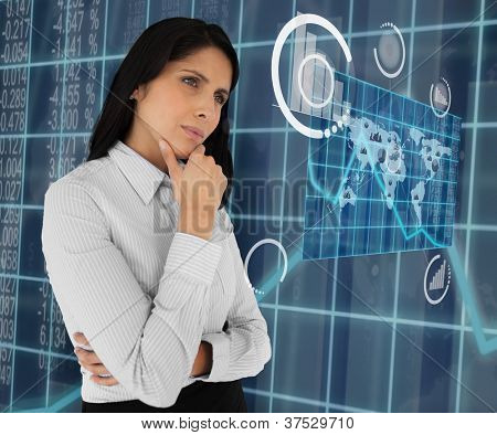 Business woman standing thinking and looking at holographic world map