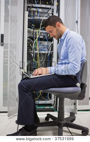 Man on his laptop beside servers in data center