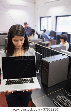 Woman showing a laptop in computer class