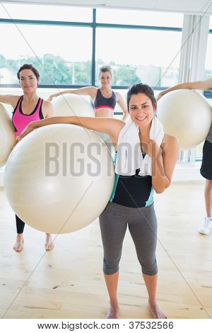 Women holding exercise balls at the gym
