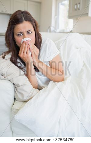 Woman feeling sick and lying on the sofa