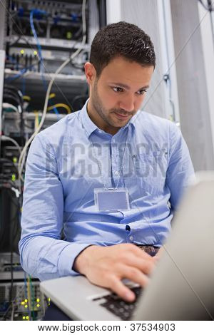 Man working on laptop in front of servers in data center