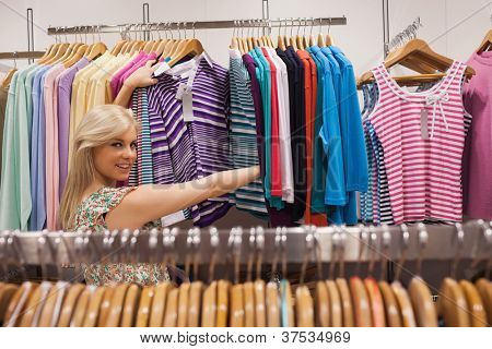 Woman looking at a clothes rack of a boutique showing clothes