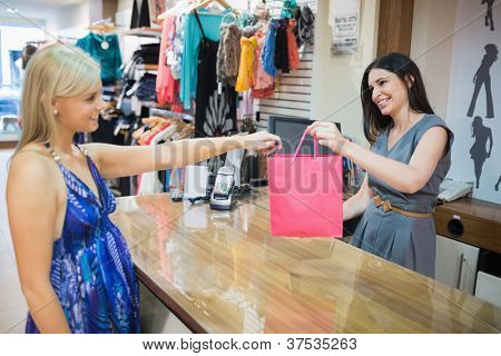 Woman handing over shopping bag at chas register in clothes store