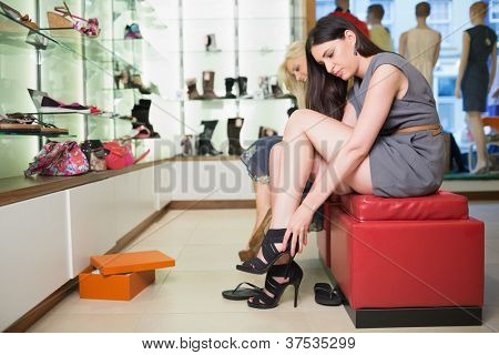 Woman trying black shoes sitting in a shop