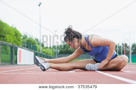 Woman stretching on a track in a stadium
