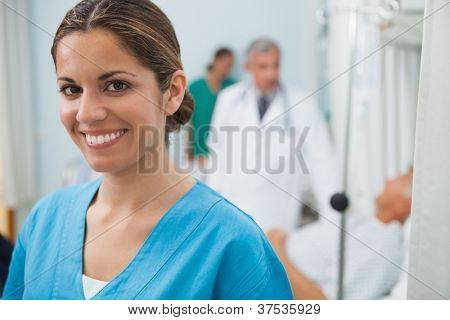 Smiling nurse in hospital room with doctor, patient and other nurse in background