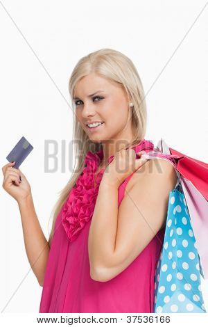 Blonde holding shopping bags and a card against white background