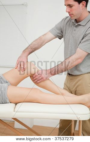 Serious brunette doctor holding the knee of his patient in a room