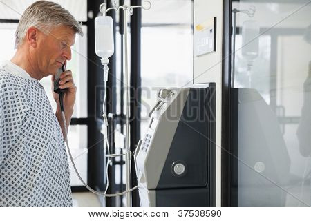 Patient with I.v drip on payphone in hospital corridor