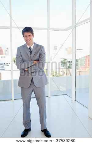 Happy businessman crossing his arms and standing with a view of the city behind him