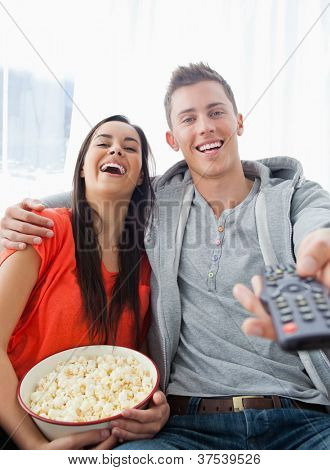 A couple sitting on the couch laughing as they have popcorn and look into the camera