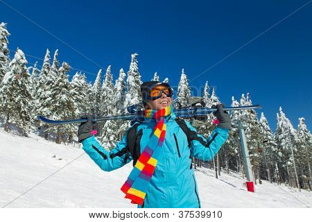 Young male skier holding ski; blue jacket; black pant; horizontal orientation