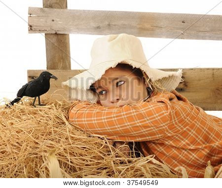 "A pretty teen ""scarecrow"" waking up to find a big old crow perched by her head."