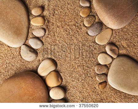 trace bare feet made of pebble stones on the beach sand background