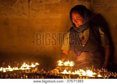 tibetan woman lights incense butter candles