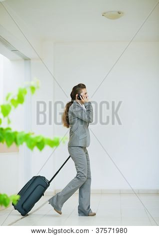 Business Woman In Business Trip With Wheel Bag Speaking Mobile