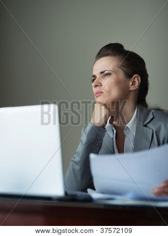 Thoughtful Business Woman Working With Documents And Laptop At D