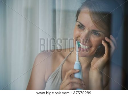 Woman Brushing Teeth With Electric Toothbrush And Speaking Mobil