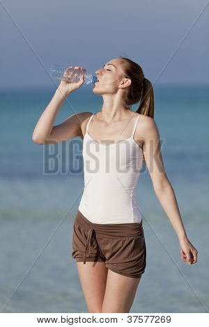 Woman Drinking Water From A Bottle On The Beach Portrait