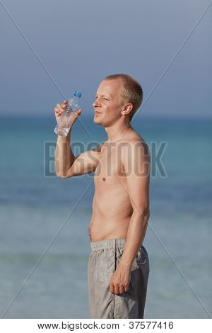 Man Drinking Water From A Bottle On The Beach Portrait