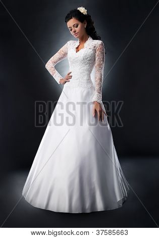 Fashionable Young Female Brunette In White Bridal Dress Posing
