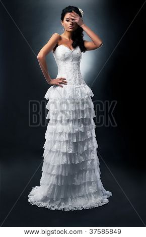 Lovely Bride Brunette In White Dress Standing In Studio Posing