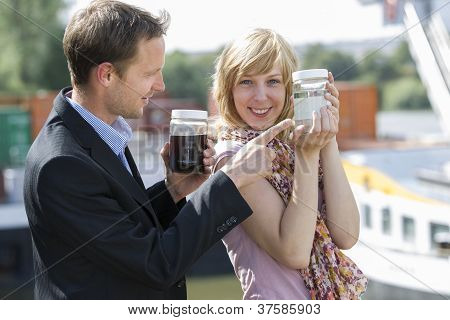 Colleagues with clean and dirty water containers from sewage treatment plant