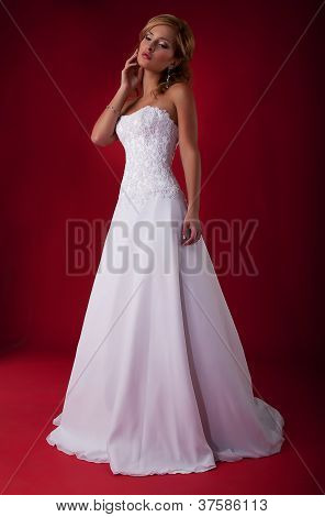 Fashionable Blonde Bride In Long White Wedding Dress Posing