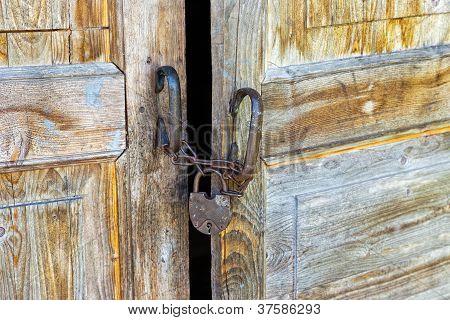 Rusty Padlock On An Old Wooden Door