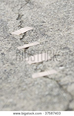 Bandages Over A Crack In The Road.