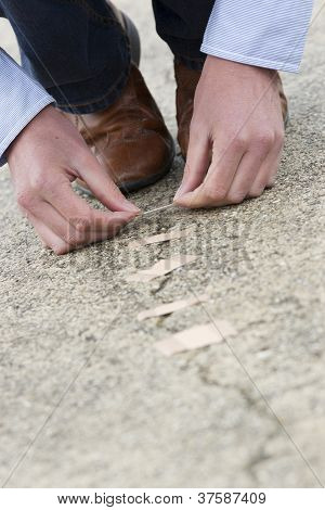 Man Applying Adhesive Bandage On Cracked Road.