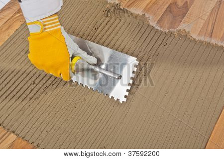 Worker Applied Tile Adhesive On Old Wooden Floor