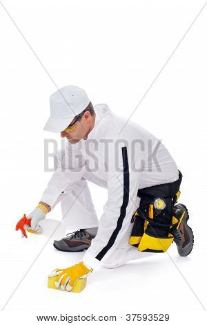 Worker Cleans The Floor With A Sponge And Spray