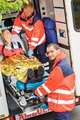 Paramedics helping woman on stretcher in ambulance smiling accident victim