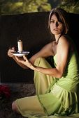foto of headstones  - A young beautiful woman holding a candle at a headstone in a graveyard - JPG