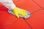 image of grout  - Hand with yellow gloves and blue towel clean red tiles grout from cementios milk before grouing - JPG