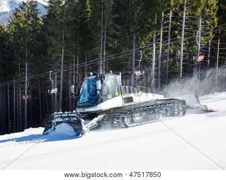 Moving piste basher on a ski slope