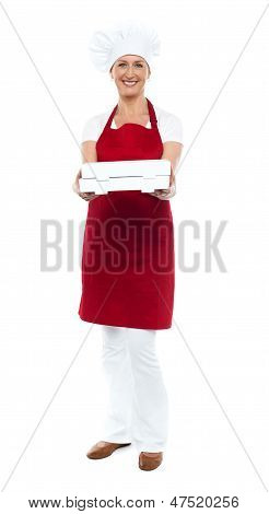 Full Length Portrait Of Woman Chef Offering Pizza