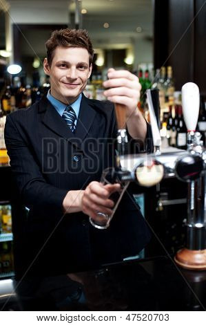 Handsome Mixologist Putting Ice Into Tall Glass