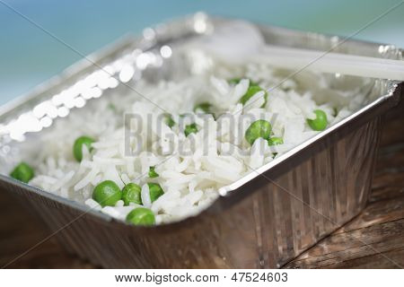 Basmati rice with green peas in the disposable aluminum pan