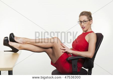 Sexy Secretary Sitting With Her Feet On The Desk
