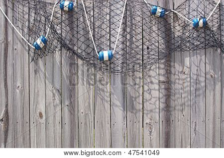 Fish Net With Floats On Wooden Fence