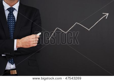 Businessman standing close to arrow sign