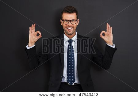 Happy businessman wearing glasses showing OK sign