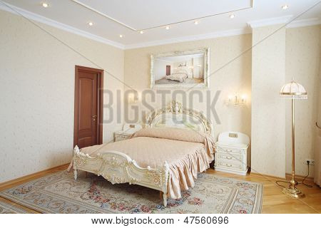 Luxurious bedroom with beautiful double bed in classic style.