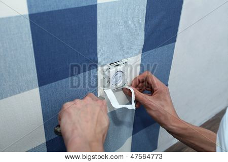 Decorator With Scalpel Hanging Wallpaper Over Wall Socket