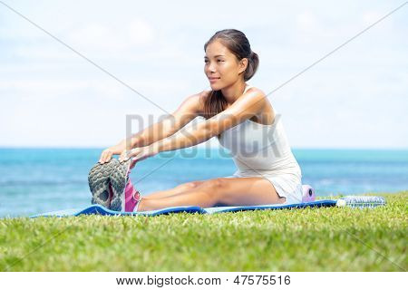Woman training fitness stretching legs exercise outside by the ocean sea. Beautiful fit female fitness girl model sitting on grass doing stretch exercising after workout. Mixed race Asian female model