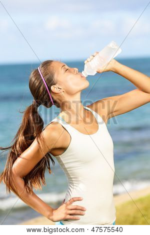 Fitness woman drinking water after running at beach. Thirsty sport runner resting taking a break with water bottle drink outside after training. Beautiful fit sporty mixed race Asian girl.