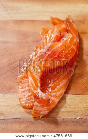 smocked salmon homemade, with spice on wooden board